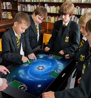A group of school children standing around a digital table learning chemistry
