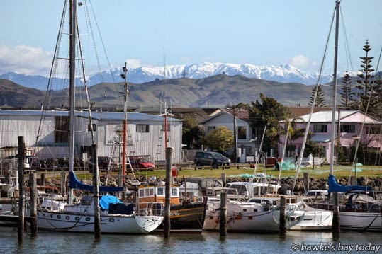 Snow on the Kaweka Range in glorious sunny weather, pictured from West Quay, Ahuriri, Napier, looking across the marina at Napier Sailing Club and Meeanee Quay. photograph