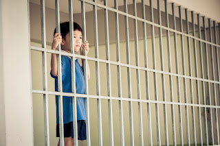 Young boys looks out from behind prison bars.