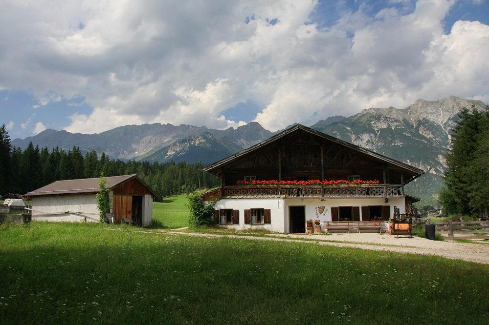 Paisagem num vale com um campo relvado em primeiro plano e logo a seguir uma casa típica do Tirol. Ao fundo uma zona de floresta e por fim as montanhas e céu nublado