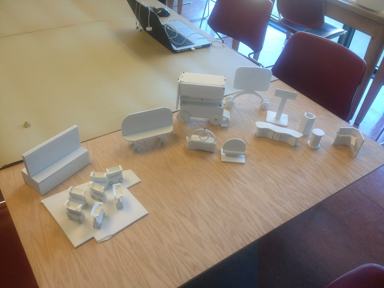 A collection of foam core model mockups are distributed on a table.