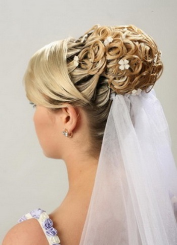 avec des mches prisent dans le postiche qui fera votre chignon ces meches seront garni avec des petites fleurs qui terminera votre coiffure de mariage - Postiche Chignon Mariage