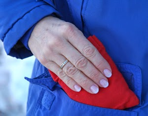Woman tucking a red Palm Pack in her pocket to keep hands warm while going for a walk in winter