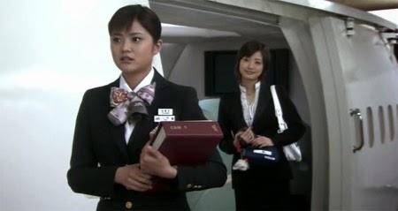 Mikami speaks to Ueno, played by Shimizu Yuki ( 清水由紀 ) at the model cabin.