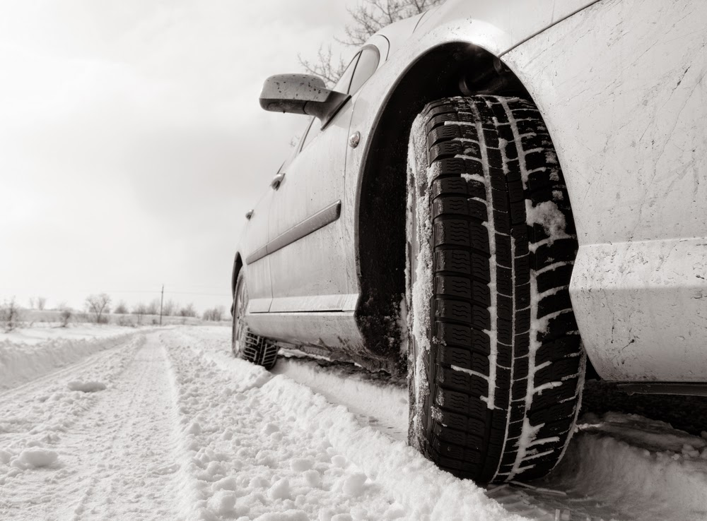 image of winter tires on car on snowy road