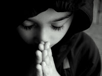 Foto de un niño en actitud reverente, sus ojos están cerrados, cabeza inclinada y las manos juntas para orar.