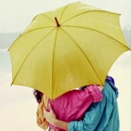 Couple in Pastel Raincoats Hugging under Umbrella