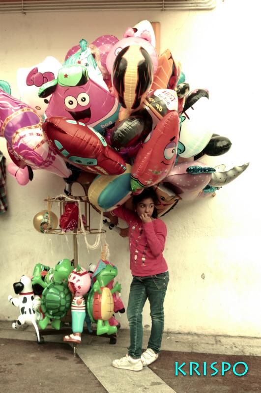 niña vendiendo globos