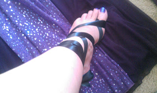 foot with painted toes and ribbons on a purple dress