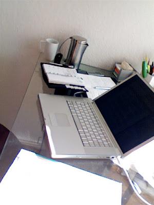 Glasschreibtisch mit Sonne darauf. Laptop, Kalender, Teekanne, Stifte, Notizzettel, angeschnitten Wörterbücher, Notizbuch