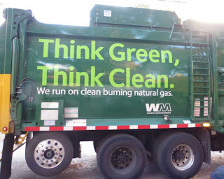 Side of green Waste Management garbage truck with huge letters reading