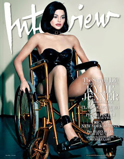 Photo of Kylie Jenner on the cover of Interview .magazine siting in a gold wheelchair with her arms resting on the wheels, wearing black heels, and a black corset)