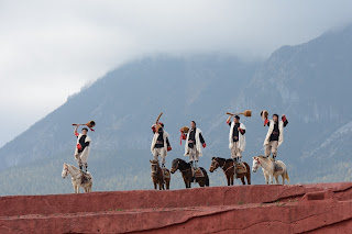 Men standing on horses at Impression Lijiang show