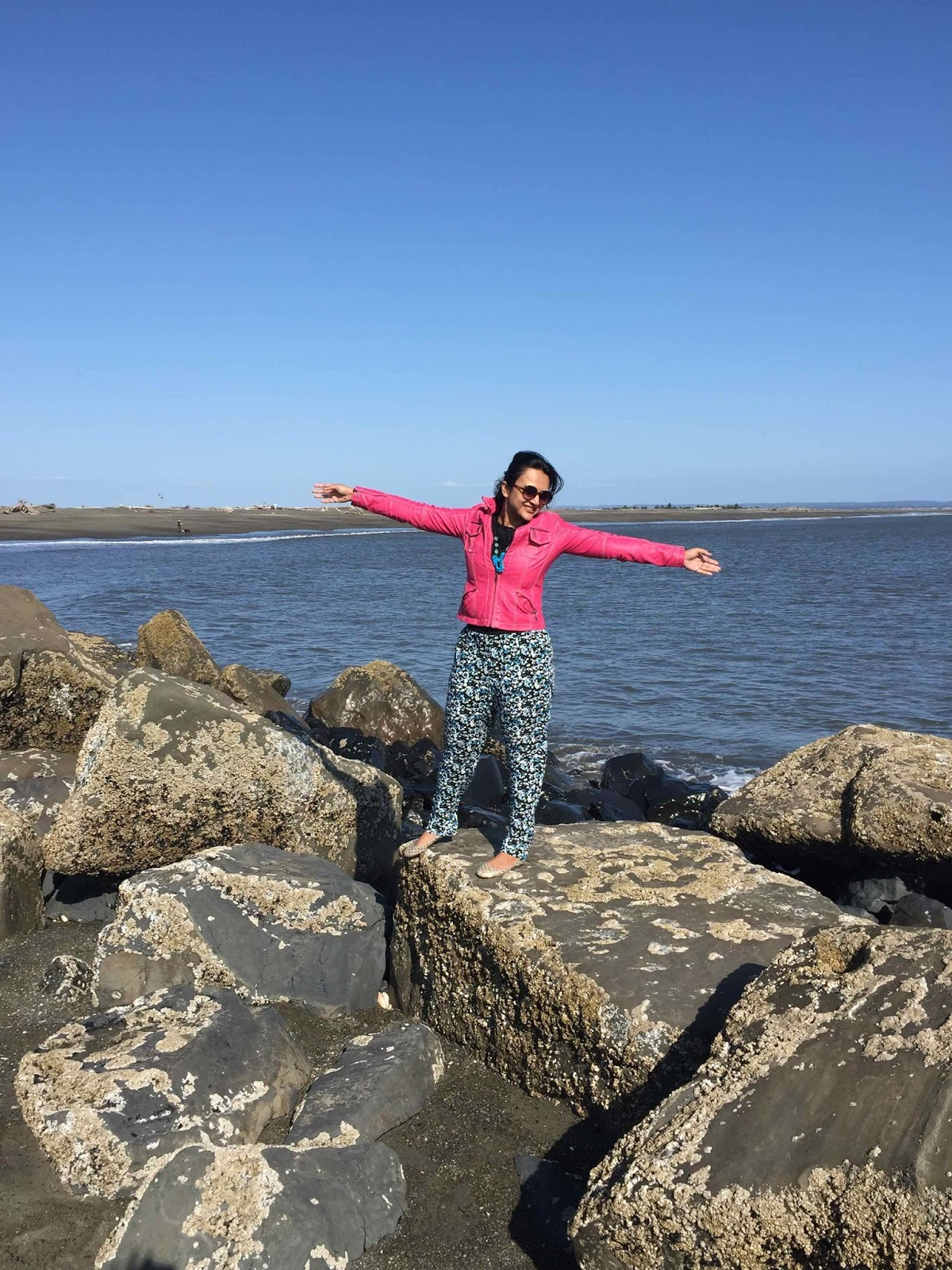 floral pants, printed pants, pink leather jacket with printed pants, ocean shores, girl on a beach
