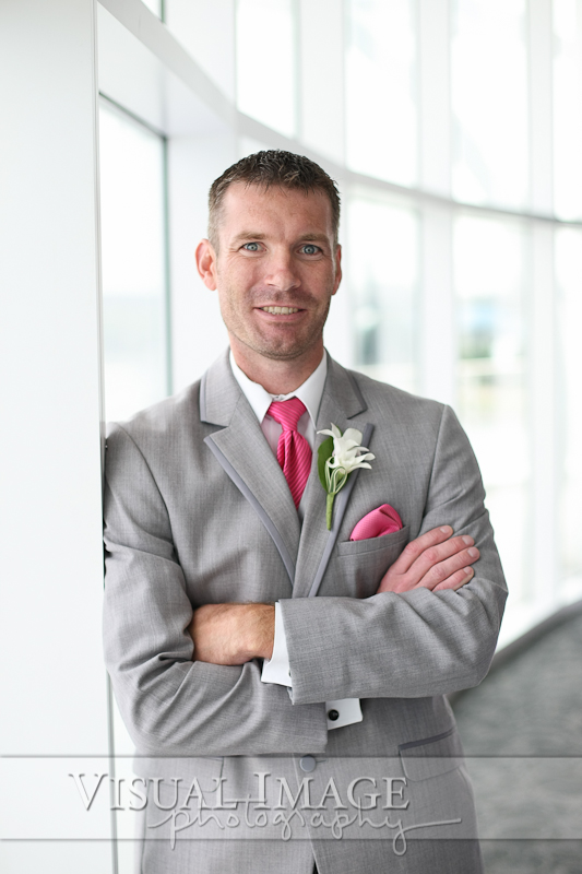 Groom wearing gray suit with pink tie