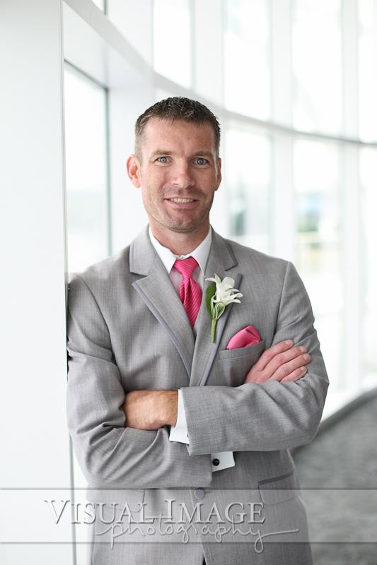 Groom wearing gray suit with pink tie