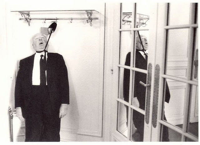 Alfred Hitchcock hanging by two neckties
