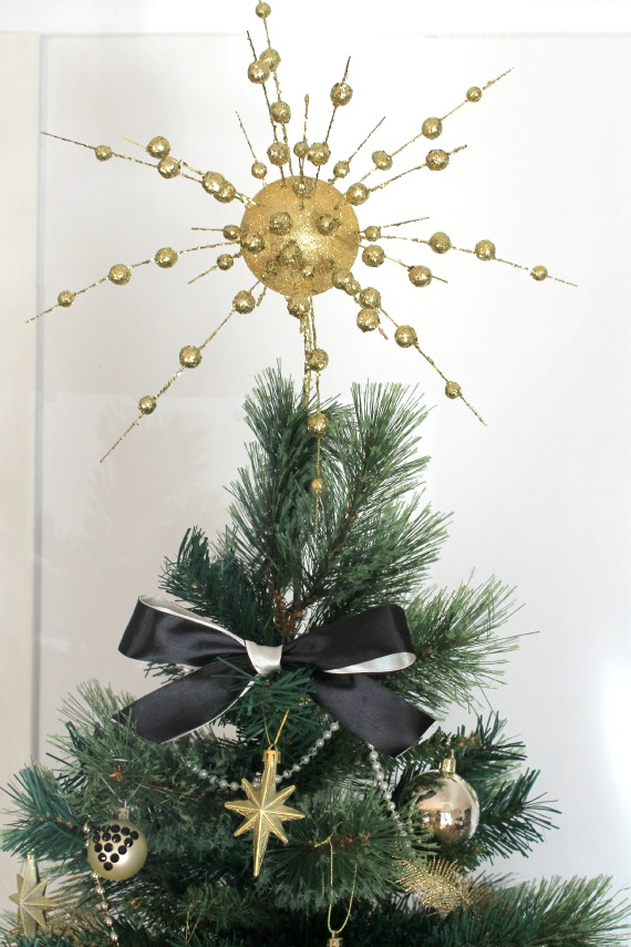 photo of christmas tree with handmade diy gold starburst tree topper