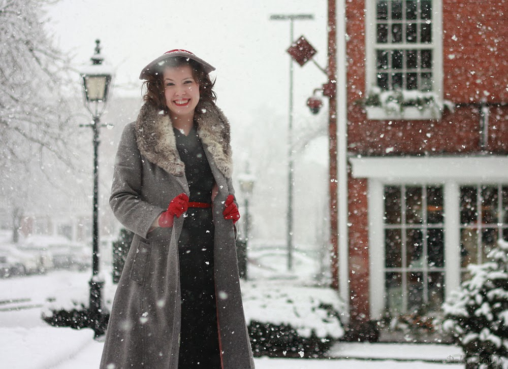 Frances standing outdoors in the snow wearing a grey cap, red gloves, and a fur-collared coat