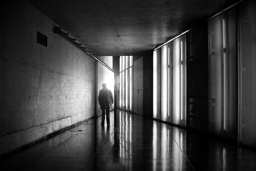 Corredor a afunilar e um homem perto do final com uma luz forte a incidir nele.