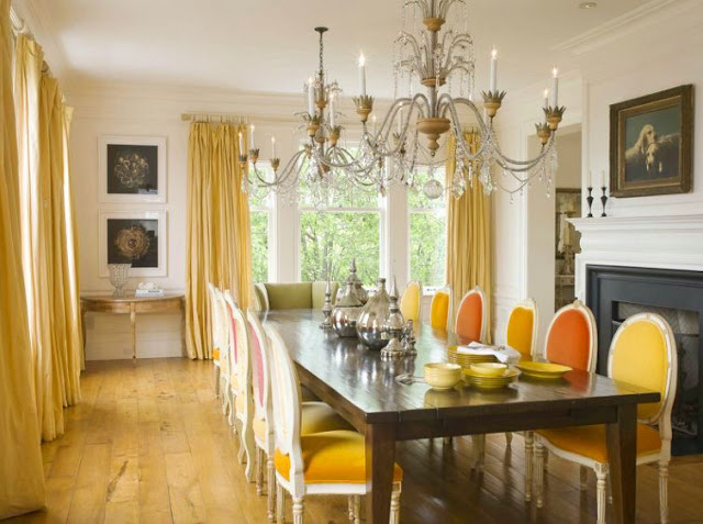 formal dining room in a san francisco mansion with orange and yellow upholstered louis XIV chairs, a dark wood farmhouse style table, wide paneled wood floor, floor length yellow curtains, two chrystal chandeliers and a fireplace with black molding and a white mantel