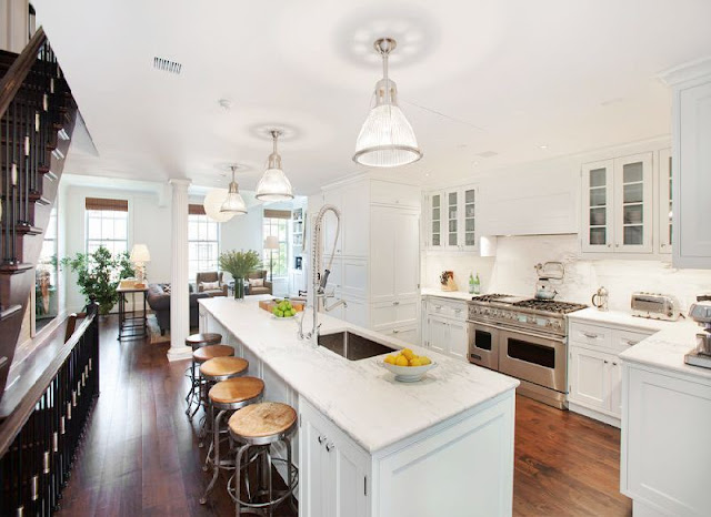 open kitchen with marble counters, stainless steel appliances, an island with metal barstools and stained wood floor