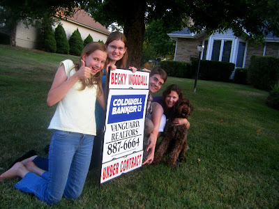All 5 of us are gathered, kneeling, around a realtor's sign in the front yard; Katharine is giving a big thumbs-up, Charissa is smiling, Tim and I are pointing at the words Under Contract, and Alfie is sitting and smiling too!