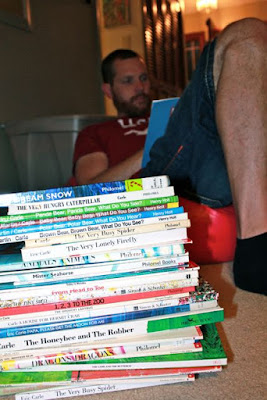 Reading a stack of books by Eric Carle