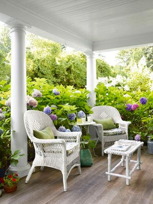 White wicker furniture surrounded by lush greenery makes this front porch decor feel like a sweet hide-away