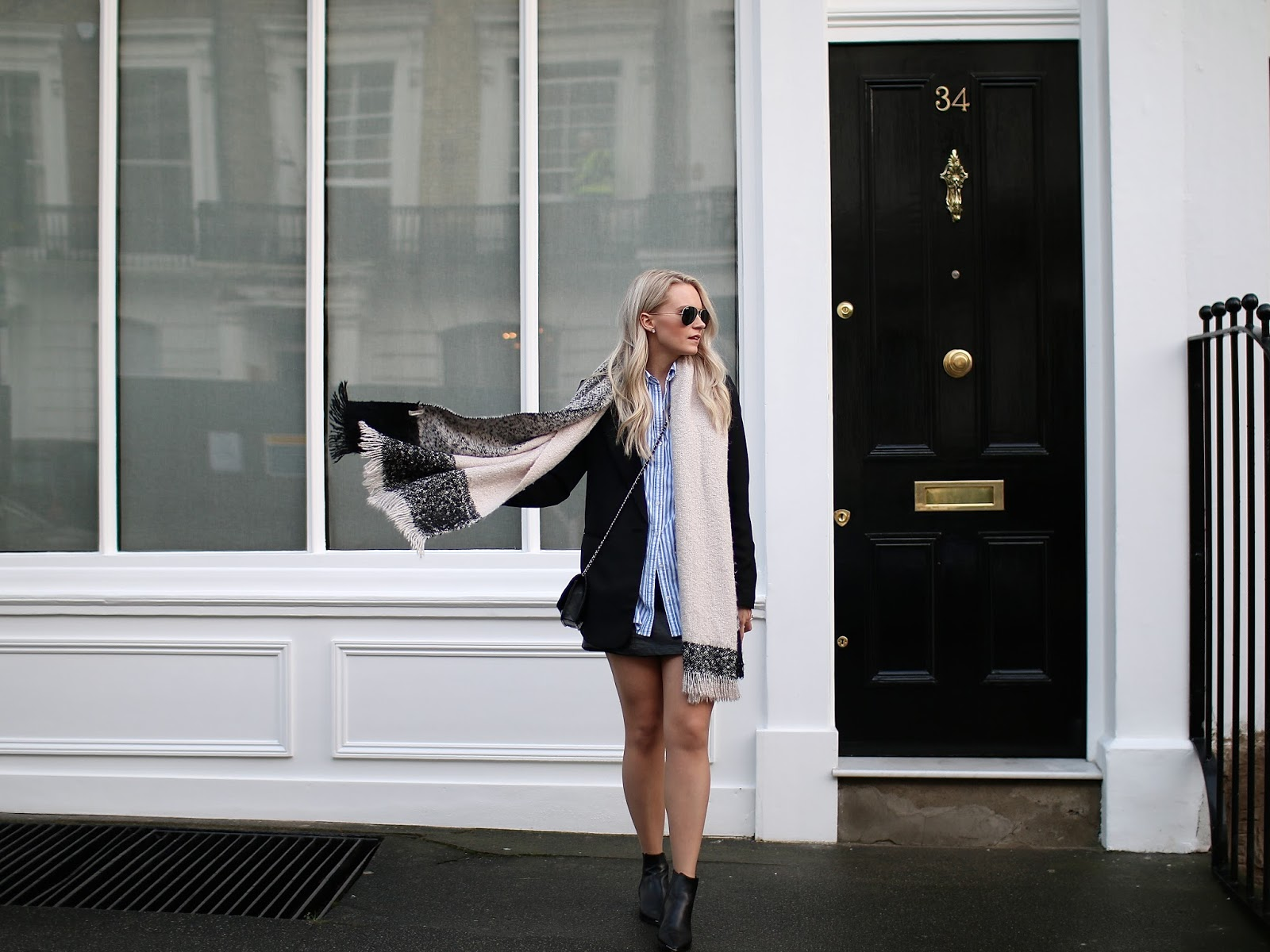 a blond women wearing striped button down shirt on notting hill, flips her scarf in the wind