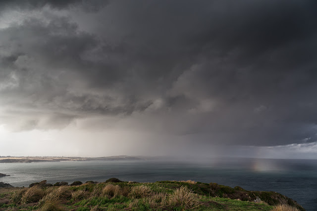rain cloud with rainbow over sea