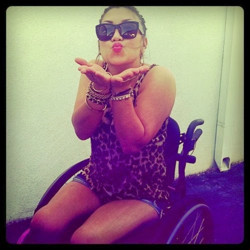 Young woman in a manual wheelchair, wearing a leopard print short top and dress combo, wearing sunglasses, blowing a kiss