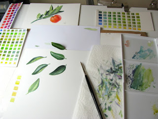 Artist desk with colour charts and watercolour studies of a leaf