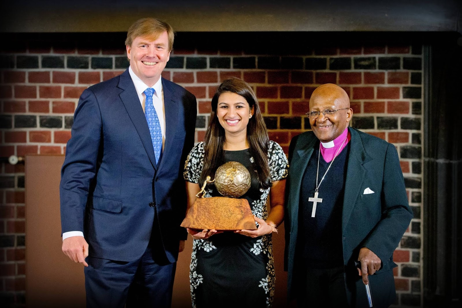 Dutch King Willem-Alexander and South African Archbishop Desmond Tutu pose with American Neha Gupta