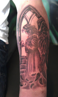 arm tattoo: Angel of Death portrayed as a blindfolded little girl with giant black feathered wings