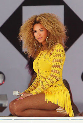 Fashionista and singer Beyonce glamorous style outfits blonde curly hair and yellow dress in concert.