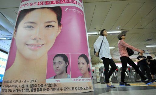 Before and after photos of plastic surgery displayed in a subway station
