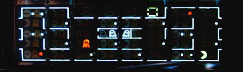 [Image: The display with parts of it glowing brightly, namely the walls of the scene, the main character in one corner, power-up pills everywhere and three ghosts near the middle. The score counter is showing zero.]