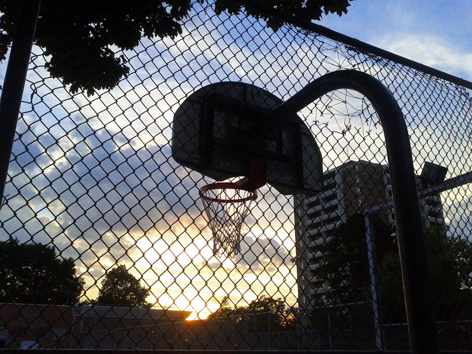 Stock photo: Basketball net behind a cage with the clouds and sun in the background