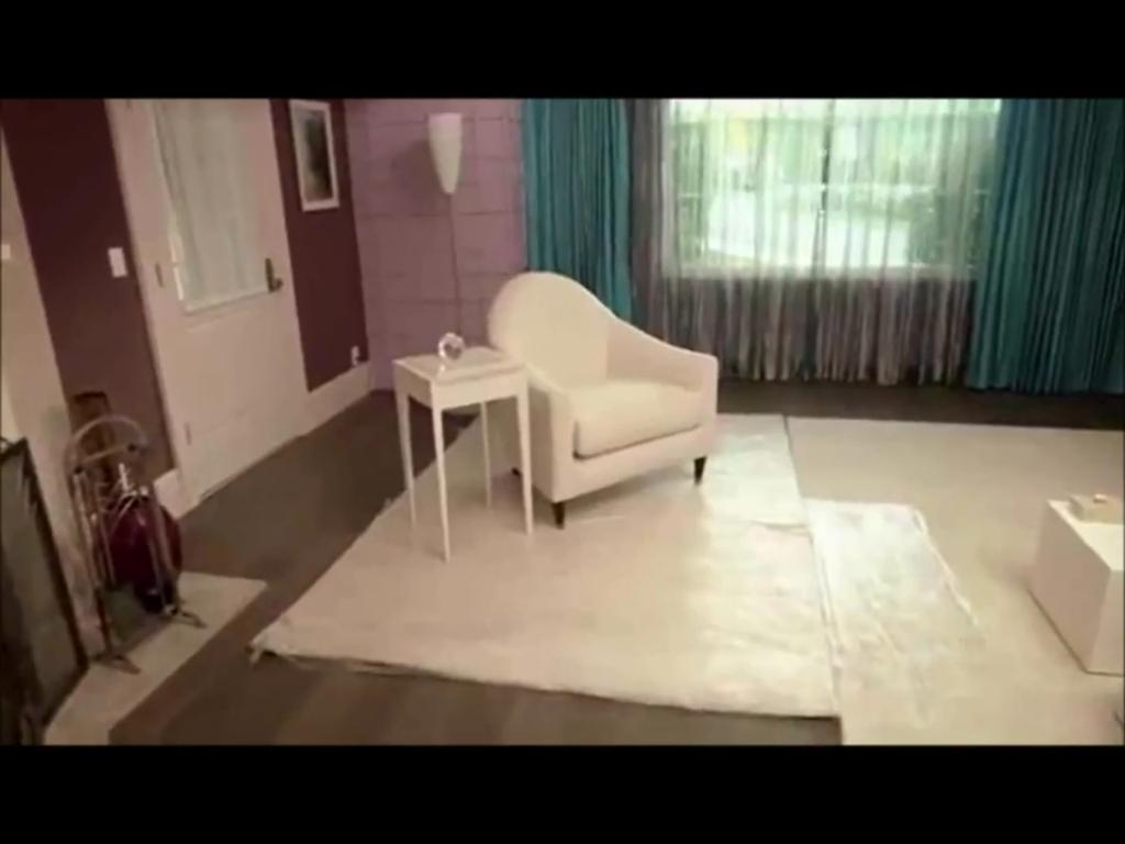Un petit fauteuil blanc est installé à côté de la cheminée un guéridon est posé juste à côté les rideaux sont du même bleu que les fauteuils d