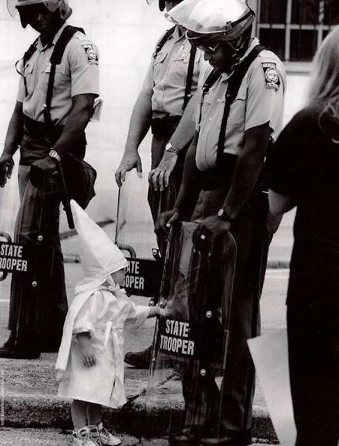 عجائب الدنيا وهل تعلم - طفل أبيض وقوات من الشرطة السود خلال احتجاج كو كلوكس كلان.