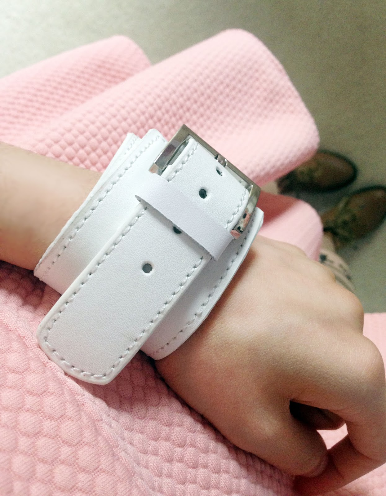 Close-up of the Chicnova white wide leather bracelet with pin buckle detail and the pure color elastic waist skirt in pastel pink
