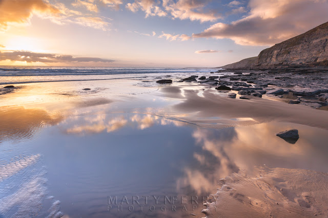 Clouds reflect in the ocean at Dunraven Bay in South Wales by Martyn Ferry Photography