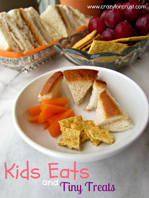 A plate of kids sandwich, carrot sticks and crackers.