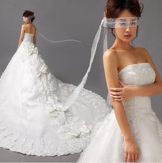 Vestido de novia princesa strapless, sin mangas, con apliques de flores con detalles plateados y una gran cola con lazos