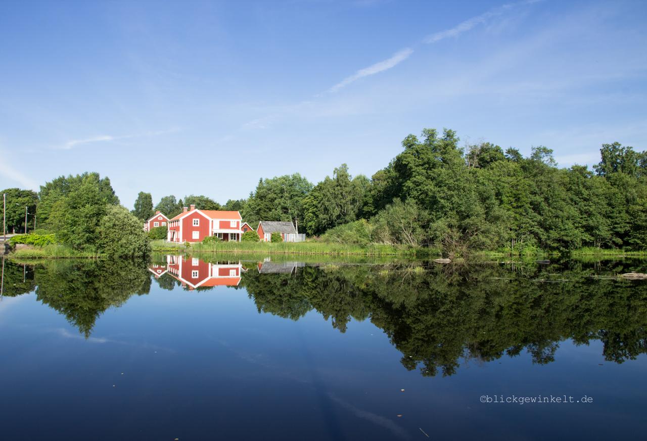 Rotes Haus vor stahlblauem Himmel und See