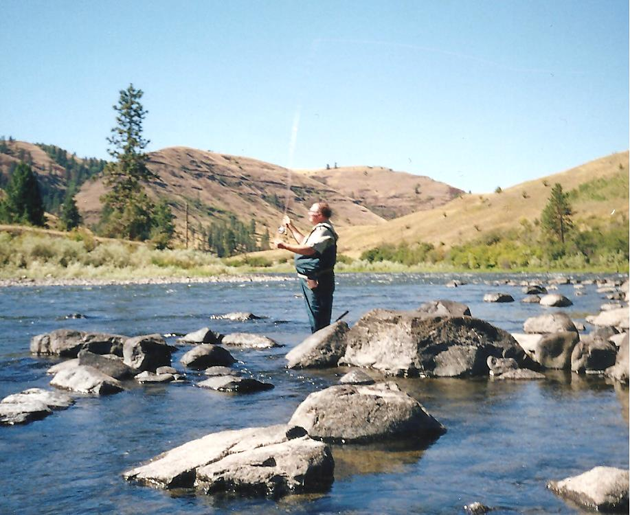 Man fly fishing among boulders in a river in the high desert of eastern Oregon.