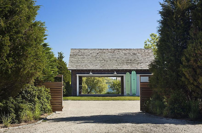 Gravel driveway surrounded by trees leading up to a lake house in Montauk on Long Island