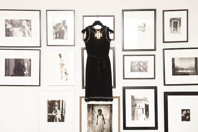 black Oscar de la Renta dress hangs over a collection of framed black and white photos on a wall