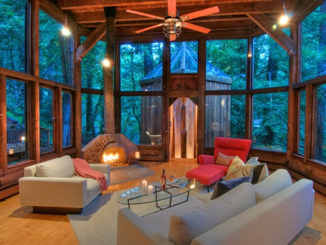 Photo of living room and the fireplace inside of tree house in the forest